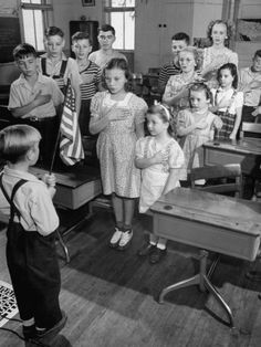 fdde066121c Children Reciting the Pledge of Allegiance as a Boy Holds the Us Flag in  their Classroom Photographic Print by Bernard Hoffman at AllPosters.com