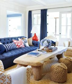 This Coastal Living Room Is Framed With Navy Draperies And Anchored With A  Navy Sofa. The Sofa Is Filled With Red, White And Blue Pillows.