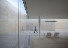 Glass building behind a sandstone enclosure to match a cathedral in Zamora by Alberto Campo Baeza.