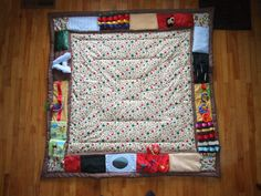 Baby play mat, with different textures, a mirror, a corduroy and furry patches, a squeaky velour patch, one with jingle bells, ribbons, pockets for hiding toys, teether, and rattle.  A baby gift not like any other