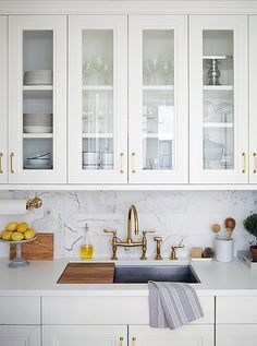"""Rich materials including brass and marble accent the kitchen. """"Brass is such a warm metal,"""" says Vivian """"One of the ways we accomplished that warm feeling in the apartment was by using brass."""""""