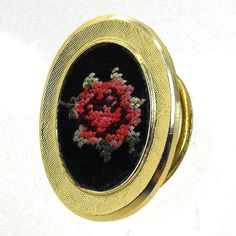 """Vintage signed Western Germany dress clip with a hand stitched petite point rose flower in red and pink on black fabric. Hand work is mounted in a gold plated frame. Maker: Western Germany material: fabric Approximate Size 1 3/8"""" x 1 1/8"""" Condition: very good pre-owned Your purchase will be shipped in an attractive jew"""