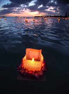 Honolulu, Hawaii: a lantern draped with a flower lei floats on the water during the Na Lei Aloha Lantern Floating event held by the Shinnyo-en Buddhist organisation at Ala Moana beach park during Memorial Day. The event is held in honour of those killed by war, natural disasters and ill-health
