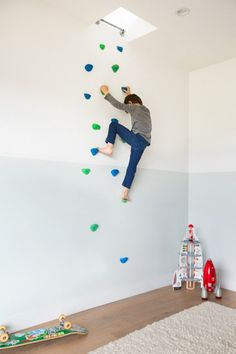 Boy on climbing wall in bedroom with two-toned walls in Murnane House in Los Angeles by Project M Plus   Remodelista