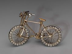Bicycle brooch, mid–1890s, gold, diamond & ruby, English.  This is a brooch for someone who is at the cutting edge of female cycling fashion, has considerable wealth, and chooses to make a statement about the new found freedom of woman at the height of the suffragist movement. | Museum of Fine Arts, Boston