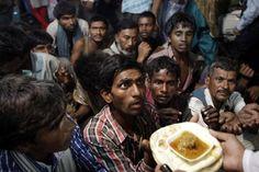 Hindúes Sin techo esperando para recibir comida gratuita distribuida en la mezquita de Eid al-Fitr, Nueva Delhi, India