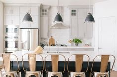 Beautiful kitchen features light gray cabinets painted Benjamin Moore Mindful Gray paired with Caesarstone Organic White countertops and a white marble subway tile backsplash.