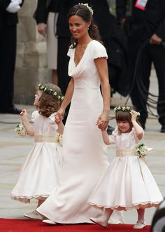 The white Alexander McQueen bridesmaid dress Pippa wore to Prince William and Kate Middleton's wedding in 2011 almost stole the show. The frock—and her svelte figure—made her an instant fashion celebrity. Pippa has Grace Van Cutsem (R) and Eliza Lopes (L).