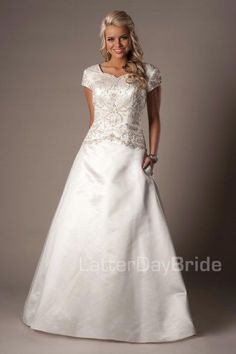 Lansbury   Modest Wedding Dress   Modest Wedding Gown   LatterDayBride   LDS   SLC   UT   Salt Lake City   Utah   Worldwide Shipping    The jewel-encrusted bodice features dramatic lines, both in the sweetheart neckline and the Basque waist. Buttons line the length of the train and the pleating in the rich satin skirt call back to a royal era. The dress also features pockets! Gown available in Champagne/Silver, Ivory/Silver, Diamond White/Silver, White/Silver, White/White…