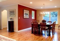 This room is Accented because the floor and back wall are light brown and then the wall and chairs are a dark red.