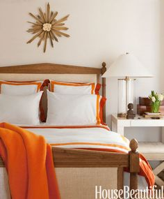 Orange bedding accents brighten a white guest room in this San Francisco row house by designer Benjamin Dhong.