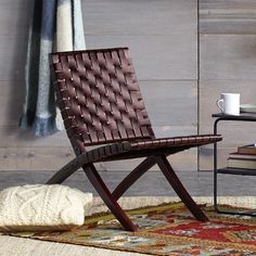 "WYATT CHAIR -- Durable stained and polished sheesham wood is hand woven with leather straps in this comfortable, generously roomy folding chair. A versatile home décor update, whether your style is contemporary or rustic. Powder coated hardware. Imported. 21-1/2""W x 35-1/2""D x 31""H, seat 16-3/4""H."