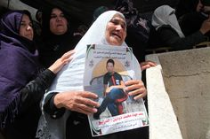 Mourning woman holds poster of slain child ... Israeli forces kill 2 West Bank youths in ONGOING ATTACTS!!!! ... kd