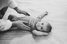 A lifestyle photograph of a baby getting changed out of his pyjamas during an in home documentary family photo session in Boston, Massachusetts - Gina Brocker Photography
