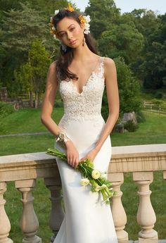 This wedding gown is made for the minimalist looking for some extra glam on her big day! With its plunging v-neckline, fitted lace appliqué bodice, sheath silhouette, and chapel train, this wedding dress is flawless for photogenic moments. Complement it with silver heels, a lace appliqué and tulle flower girl dress, and one shoulder bridesmaid dresses. #camillelavie