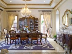To match the scale of the formal dining room, designer Lori Dennis hangs heavy brocade curtains right below the tray ceiling. A simple ring heading is used to balance the luxurious fabric, while silk ties hold the draperies back to allow natural light into the space.