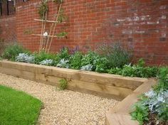 Raised garden along a brick wall adds color