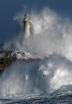 A lighthouse off the coast of Spain is battered by stormy ocean waves