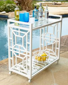 Chinoiserie Bar Cart at Horchow with white frame and casters. Two glass shelves with 3/4 perimeter rail on top.