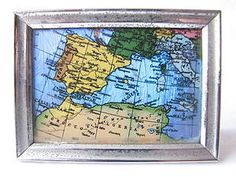 Vintage Deco Butterfly Wing Picture Map The frame is made from silver tone metal and has rust spots around it.  The back has a good sprung wooden prop to keep it upright. A label says Real Butterfly Wings hand painted in oils Made in England patent 202213.  9 x 6.5cm