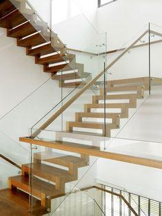Стильная деревянная лестница с стеклянными перилами и несколькими пролетами.