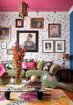 colorful bohemian living room with pink ceiling green sofa and gallery wall