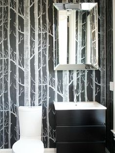 Small bathrooms are a great place to try a striking black-and-white wallpaper.