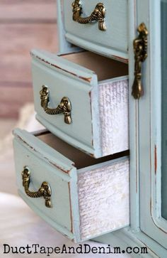 Decoupaged drawers on blue jewelry box with mirror makeover. Another thrift store find on DuctTapeAndDenim.com #thriftstorefind #thriftstoremakeover #thriftstoredecor #chalkpaint #DIY #paintedfurniture #decoupage #jewelrycabinet #jewelrycabinetmakeover