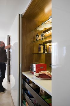 hidden appliance cabinets are concealed behind large sliding doors with sensor operated concealed LED lighting by Minosa