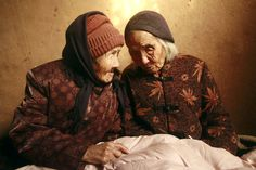 """""""Chinese 104-year-old twins, Cao Daqiao (senior, right) and Cao Xiaoqiao talk at home in Weifang, east China's Shandong province on November 29, 2009. According to the Shanghai Guinness World Records, these twin sisters, who were born in 1905, are the oldest living twins in the world as they are also listed on the Guiness World of Records for the oldest twins."""""""