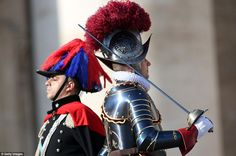 A Swiss guard and a Carabiniere stand back to back as they both attend Pope Francis'  'Urbi et Orbi' blessing message in St Peter's Square
