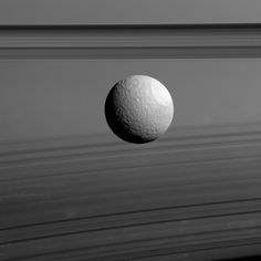Ices and Shadows: Saturn's moon Tethys appears to float between two sets of rings in this view from our Cassini spacecraft but it's just a trick of geometry. The rings which are seen nearly edge-on are the dark bands above Tethys while their curving shadows paint the planet at the bottom of the image. Tethys (660 miles or 1062 kilometers across) has a surface composed mostly of water ice much like Saturn's rings. Water ice dominates the icy surfaces in the the far reaches of our solar system…