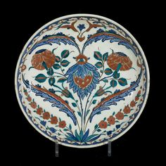 IZNIK DISH Turkey, circa 1565 The dish decorated with a symmetrical design of four saz leaves forming a heart shape around a composite flower and flanked by rose branches. This plate with its central design of symmetrical saz leaves forming a heart shape and the use of a distinctive shade of turquoise green is typical for the production in Iznik in the 1560s. However, this plate is distinctive and quite rare because it does not have a rim.