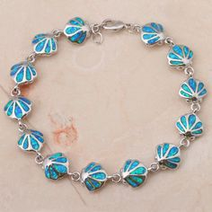 Adorned with seashells, this blue opal bracelet offers seaside style. BRACELET DETAILS - Length: 7.5 in. - Clasp: lobster-claw - Metal: rhodium-plated sterling silver STONE DETAILS - Stone type: blue