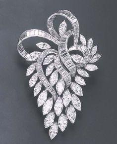 A DIAMOND BROOCH Designed as a baguette-cut diamond ribbon, extending a marquise-cut diamond openwork cascade, mounted in platinum