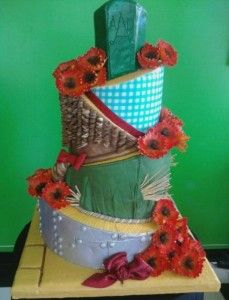 """From a David Tutera wedding: """"The wedding cake incorporated many elements from the """"Wizard of Oz"""" movie. The base is the yellow brick road, the bottom cake is the Tin Man, the next up the Scarecrow, then the Cowardly Lion, the blue check from Dorothy's dress with a glittery ruby red band representing her slippers, and the Emerald City with the bride and groom's initials at the top."""""""
