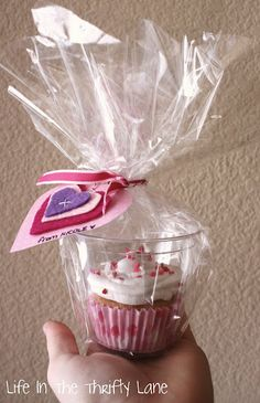 Place cupcakes in a plastic cup and wrap with cello and ribbon.  Love this idea!