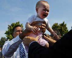 """reuters: """" Republican presidential candidate and former Massachusetts Governor Mitt Romney passes a crying baby """""""