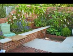 Simple Water Feature Design Ria using recycled bricks, concrete capping, timber seat and cottage garden