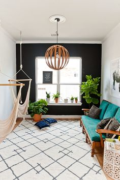 Statement wall in a bohemian living room. Love the turquoise couch