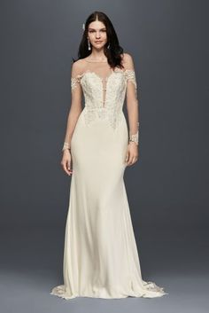 The appliqued illusion sleeves of this crepe wedding gown create an elegant off-the-shoulder look, as the train's cutout details offer a modern take on lace.   Galina Signature, exclusively at David's Bridal Polyester Sweep train Back zip; fully lined Dry clean Imported Also available in extra length and petite