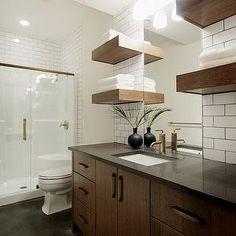 Veranda Interiors - bathrooms - glass shower, brass trim, brass glass shower, black bathroom floor, brushed gold faucet, extra-wide bathroom...