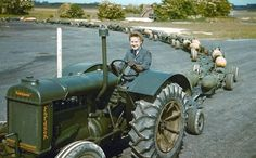 A WAAF (Women's Auxiliary Air Force) driving a Fordson tractor pulling a train of full GP-bomb trolleys at RAF Mildenhall. The size of bomb-bays in RAF aircraft and the perceived chance of a hit were both real considerations in this early period. During 1940, use of the smaller ordinance (over 2,000 20lb F; over 26,000 40lb GP; nearly 62,000 250lb GP) far outstripped that of the 500lb GP (just over 20,000). [Photo by Charles Brown. RAF Museum D 707906.]