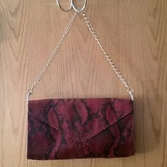 Red handbag Red and black clutch with a snakeskin look. Has chain shoulder strap that can clip on or off. One zipper pocket inside with two other pockets. Great condition from smoke and pet free home. Bags Shoulder Bags