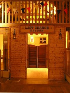 Bury Court Barn Surrey - Wild West saloon doors, copper lanterns, Last Chance Saloon sign, red, white and blue bunting and wall uplighters in amber by www.stressfreehire.com #venuetransformers