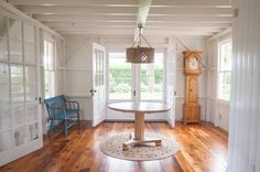 Entry hall of summer cottage, wood floors, grandfather clock and blue bench #home decor #interiors