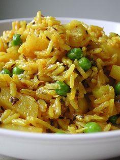 Indian rice & potatoes  2 medium potatoes, peeled and cut into sticks 3 tbsp yogurt 2 tbsp minced fresh cilantro 1 tsp ginger, peeled and minced 2 cloves garlic 1/2 tsp cayenne pepper 1/4 c dried coconut* 6 whole cloves 1 cinnamon stick 1 bay leaf 1 1/2 tsp cumin seeds 3 tbsp oil 1 cup rice 3/4 tsp turmeric 1 tsp light brown sugar 1 tsp salt 1 tsp lime juice 2 cups water 1/2 c frozen peas 1 tbsp butter