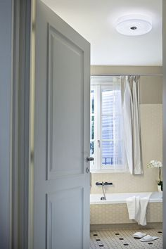 Button by Piero Lissoni complements this bright, sunlit bathroom interior featuring natural hues and a large window at Hotel Arancioamaro.