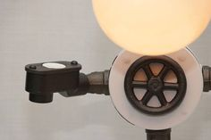 This super-cool robot lamp has it all! Not only does it have a fully-dimmable 100W G40 bulb (the dimmer knob is the cast iron valve handle on the front), but it is also your personal valet! Hold and charge your smartphone (fits even the largest smartphone with a case), charge your