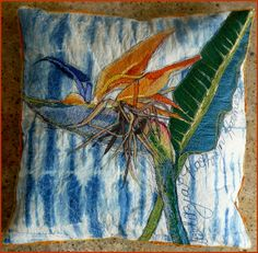 Fibre art. Strelitzia Pillow. Various fabrics and thread on indigo dyed fabric with stuffed cushion.